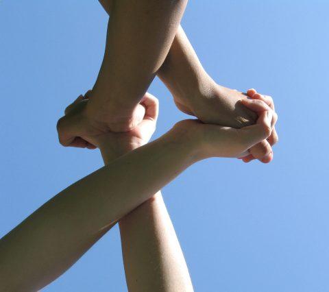 Zwei Personen verschränken die Hände